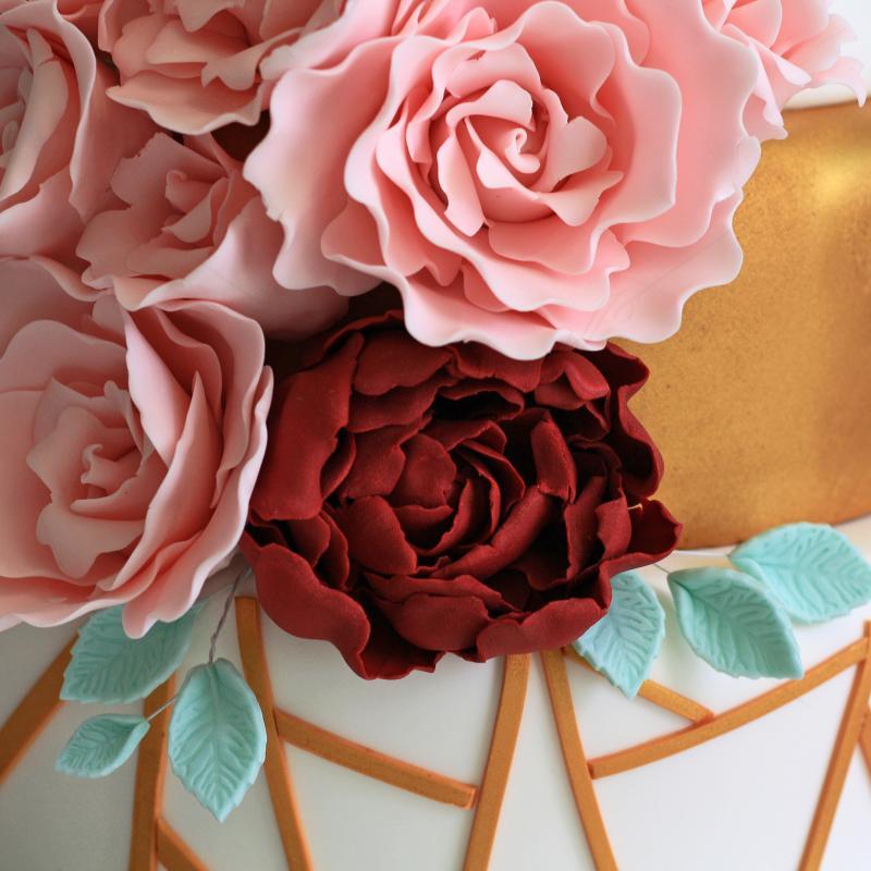 Tort de nunta modern alb cu auriu si flori roz si grena
